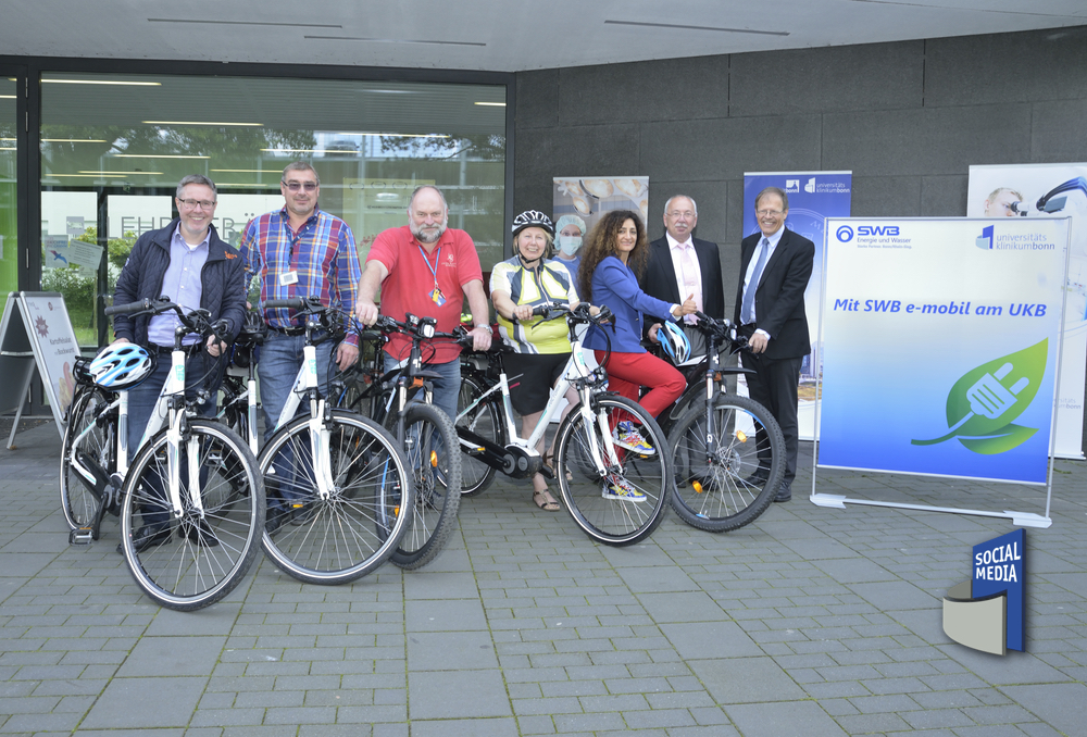 """Mitarbeiter*innen des Universitätsklinikums Bonn (UKB) nutzen """"elektrischen Rückenwind"""" für Fahrt zum Venusberg."""